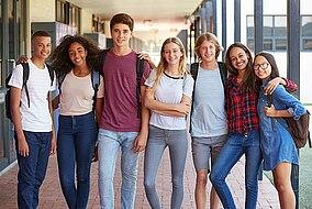 Eine Gruppe Teenager steht nebeneinander auf einem Schulflur