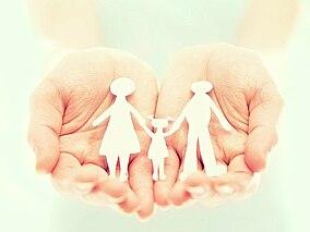 Carta tagliata a forma di famiglia, distesa nelle mani