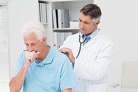 Medico che ausculta i polmoni di un uomo anziano