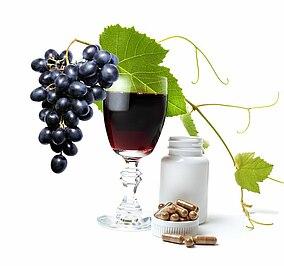 Traubenrebe und ein Glas mit einer dunklen Flüssigkeit