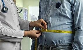 Eine Ärztin misst den Bauchumfang ihres Patienten
