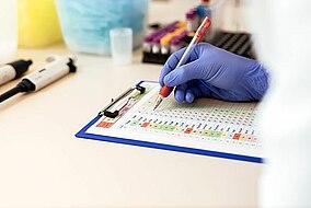 Un assistente di laboratorio annota qualcosa su un foglio per test colorato