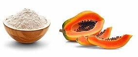 Aufgeschnittene Papaya und eine Holzschale gefüllt mit Mehl