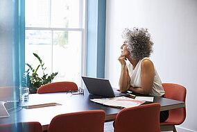 Frau sitzt mit einem Laptop am Tisch und arbeitet