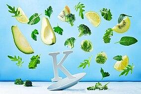 Brokkoli, Avocados, Kräuter und Kiwis um den Buchstaben K platziert