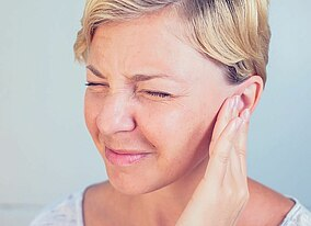 A woman with earache holding her ear.