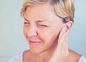 Frau mit Ohrenschmerzen greift sich ans Ohr