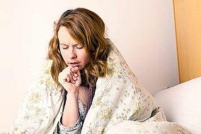 Frau sitzt hustend im Bett