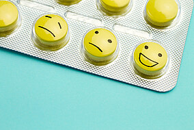 Tabletten mit glücklichen und traurigen Gesichtern