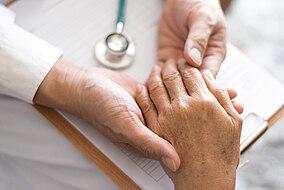 Medico che tiene la mano di un paziente con Parkinson