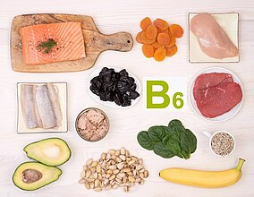 Vari tipi di carne e pesce, un avocado, frutta a guscio, frutta e verdura su un tavolo