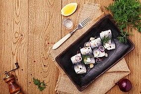Aringa con cipolle disposta su un piatto accanto a una forchetta e limone