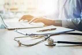 Dottore su computer portatile con stetoscopio e note accanto a se stesso