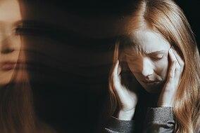 Frau fasst sich gestresst an die Stirn