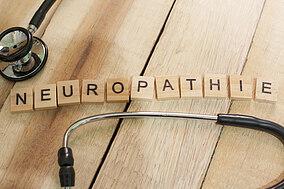 Stethoskop und das Wort Neuropathie durch Buchstaben auf Holzblöcken dargestellt