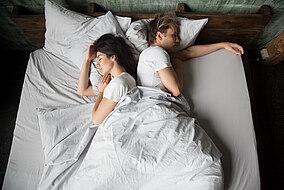 Pärchen schläft Rücken an Rücken im Bett