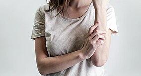 Eine Frau hat einen Hautausschlag am Arm