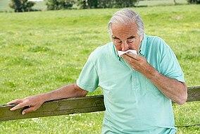 Älterer Mann lehnt sich draußen an einen Zaun und hält sich ein Tuch vor die Nase und den Mund