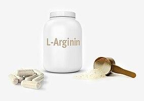 Dose mit L-Arginin Aufschrift, Kapseln und Pulver in einem Löffel auf weißem Hintergrund
