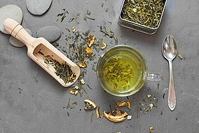 Tè verde essiccato e in infusione su una superficie di pietra