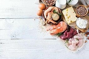 Alimenti ricchi di proteine come formaggio, uova, pesci vari e carne su una superficie