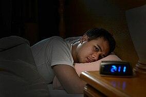 Mann nachts wach im Bett liegend mit Wecker im Vordergrund