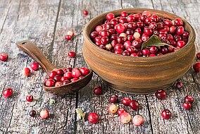 Ciotola e cucchiaio con cranberry su una superficie di legno