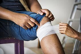 Einem Patienten wird eine Kniebandage gewickelt