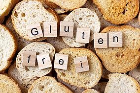 """Der Schriftzug """"Gluten frei"""" vor einem Hintergrund aus Brot"""