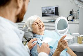Ältere Frau schau ihre neuen Zahnimplantate in einem Spiegel an
