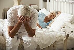 Mann sitzt enttäuscht auf der Kante von seinem Bett
