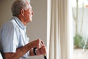 Älterer Mann mit einer Gehilfe