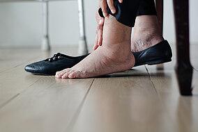 Frau hält ihren geschwollenen Fuß