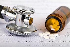 Ein Stethoskop liegt neben einer Dose Tabletten
