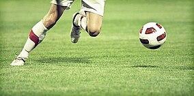 [Translate to Italienisch:] Fußballer mit Ball
