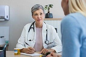 Una dottoressa parla con una paziente