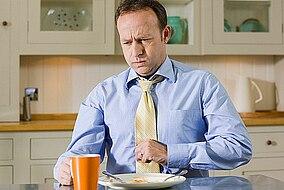 Mann sitzt am Küchentisch und hat Sodbrennen