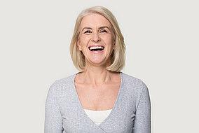 Frau lacht in die Kamera