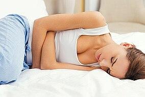 Frau liegt verkrampft auf dem Bett