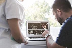 Arzthelfer schauen sich Röntgenaugnahme des Kiefers an