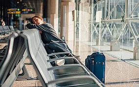 Frau schläft in einem Flughafen