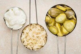 Drei Schalen gefüllt mit Sauerkraut, Gewürzgurken und Joghurt