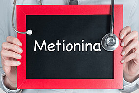 """Medico che tiene davanti al petto una lavagna con la scritta """"Metionina"""""""