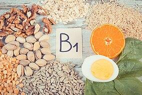 Foglio con la scritta B1 circondato da riso, frutta a guscio, uova e arance