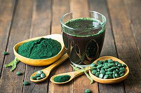 Spirulina in Tabletten-, Pulverform und mit Wasser gemischt auf einem Tisch