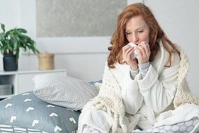 Woman suffering from a cold, sitting in bed holding tissues