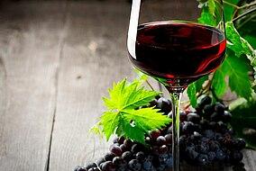 Ein Glas mit Wein und Trauben auf einem Tisch