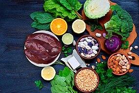 Kalbsleber, Brokkoli, Orangen, Hülsenfrüchte, Blattgemüse auf einem dunklen Hintergrund