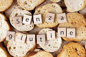 """La scritta """"Senza glutine"""" su uno sfondo pieno di pane"""
