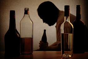 Uomo seduto in una stanza buia circondato da bottiglie vuote